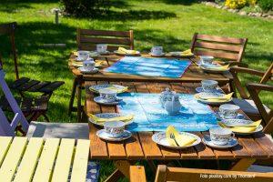 Ueblicher-Gartentisch-mit-Tassen